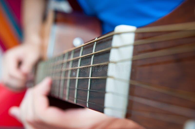den akustiska detaljgitarrgitarristen hands instrumant musikaliskt leka för aktör royaltyfria bilder
