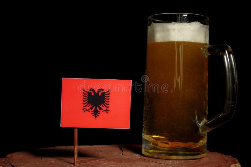 Den albanska flaggan med öl rånar isolerat på svart arkivfoton
