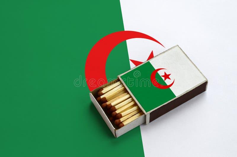 Den Algeriet flaggan visas i en öppen tändsticksask, som fylls med matcher och ligger på en stor flagga royaltyfri bild