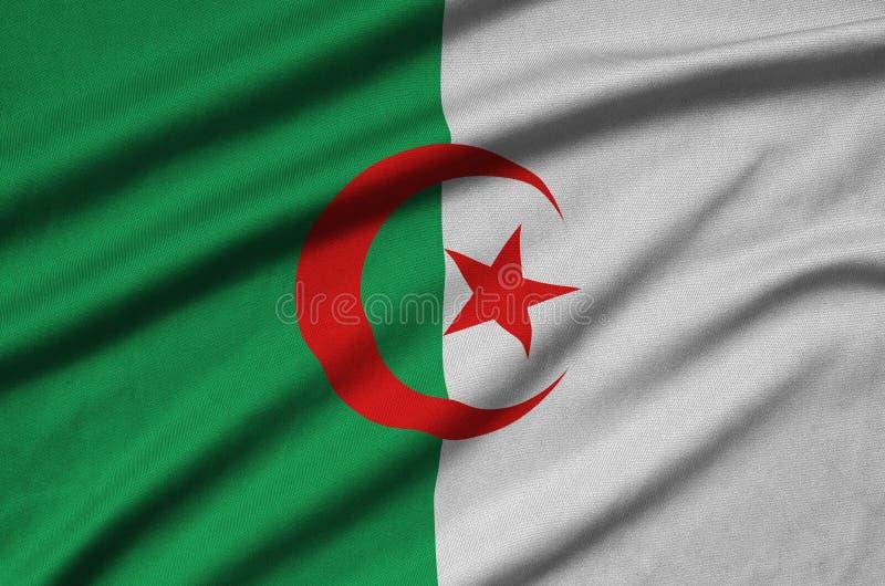 Den Algeriet flaggan visas på ett sporttorkduketyg med många veck Baner för sportlag royaltyfria bilder