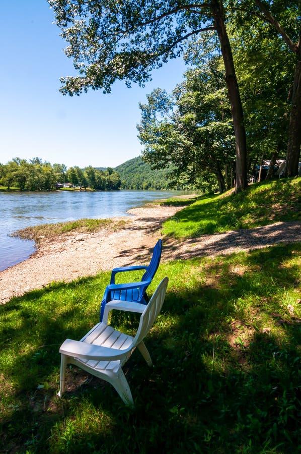 Den Allegheny floden i Warren County, Pennsylvania, USA som ses från en fodrad stenig bank för träd med en blått och en vit adiro royaltyfri foto