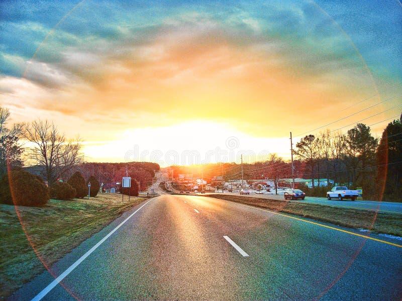 Den allsmäktiga soluppgången på universitetdrev arkivbilder