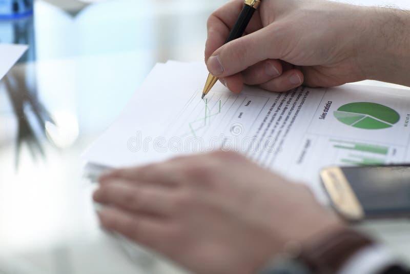 Den allvarliga affärsmannen som arbetar på att se för dokument, koncentrerade med portföljen och telefonen på tabellen arkivbild