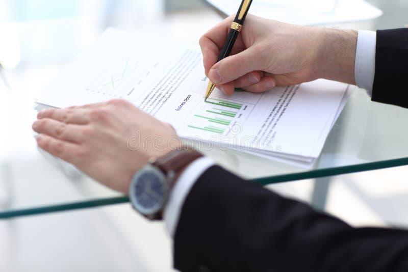 Den allvarliga affärsmannen som arbetar på att se för dokument, koncentrerade med portföljen och telefonen på tabellen royaltyfri foto