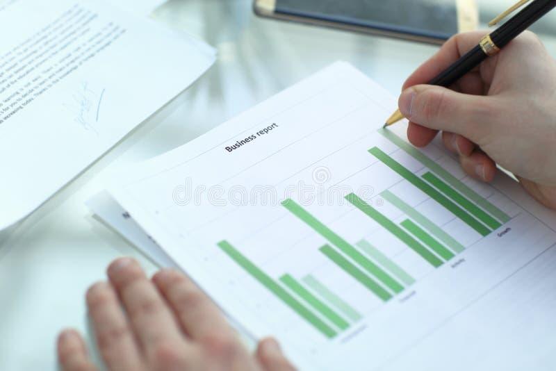 Den allvarliga affärsmannen som arbetar på att se för dokument, koncentrerade med portföljen och telefonen på tabellen royaltyfri bild