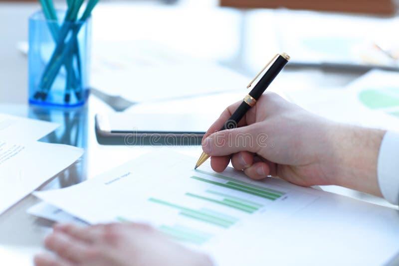 Den allvarliga affärsmannen som arbetar på att se för dokument, koncentrerade med portföljen och telefonen på tabellen royaltyfri fotografi