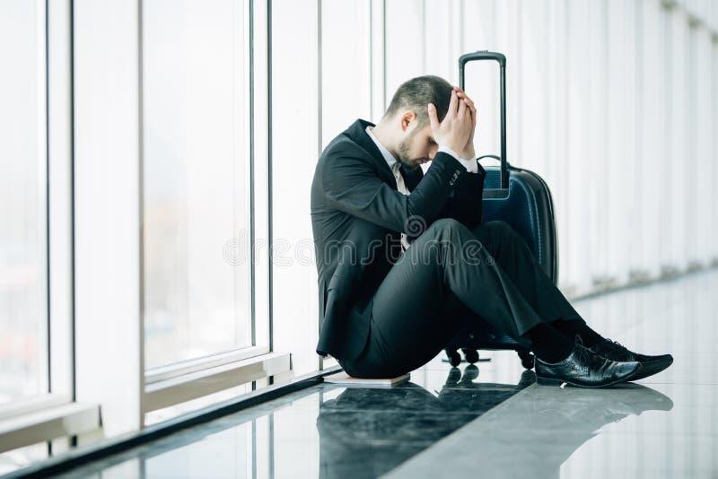 Den allvarliga affärsmannen som oroar något och att sitta och, trycker på hans huvud på flygplatsterminalen Affärsmanmiss hans fl arkivbild