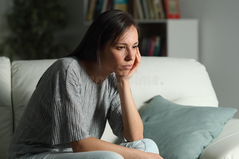 Den allvarliga eftertänksamma kvinnan ser bort hemma i natten royaltyfria foton