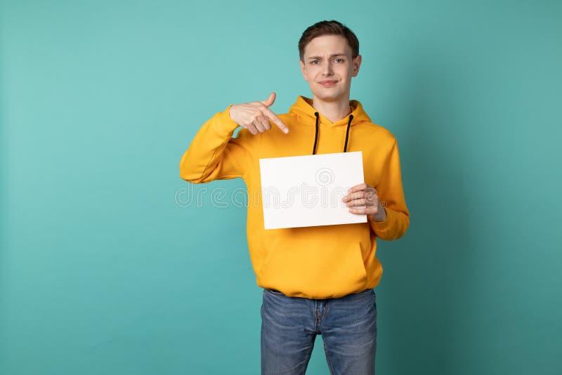 Den allvarliga eoropean mannen i gul hoodie pekar på det vita mellanrumet arkivfoton