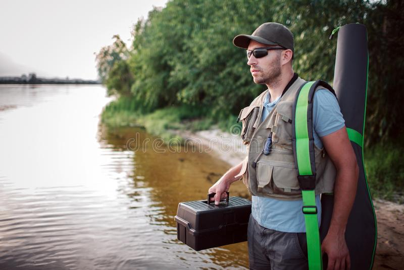 Den allvarliga fiskaren står i grunt och ser rättfram Han rymmer den plast- svarta asken i en hand och räkning arkivfoton
