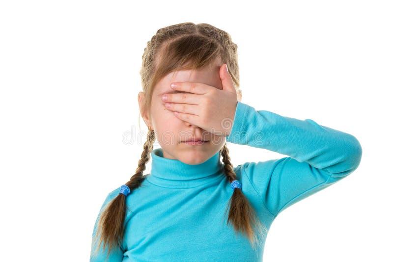 Den allvarliga flickan stänger ögon med hennes vänstra hand som isoleras på den vita bakgrunden arkivbild
