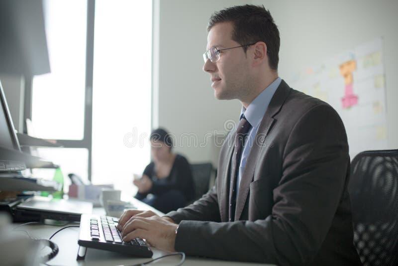 Den allvarliga hängivna affärsmannen arbetar i regeringsställning på datoren Verkligt ekonomaffärsfolk, inte modeller Bankanställ royaltyfri fotografi