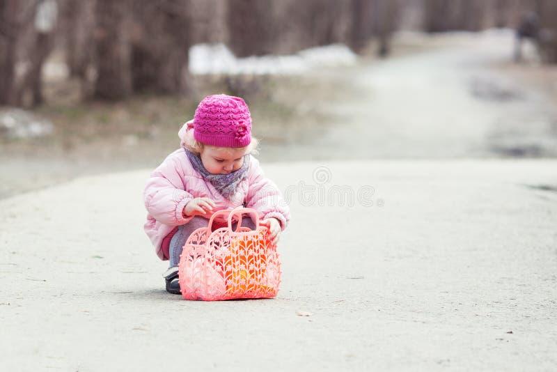 Den allvarliga härliga flickan som går med handväskan i vår, parkerar fotografering för bildbyråer