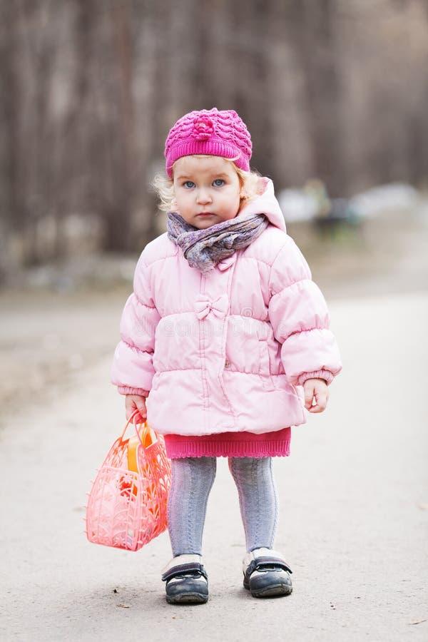 Den allvarliga härliga flickan som går med handväskan i vår, parkerar arkivfoton