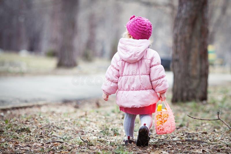 Den allvarliga härliga flickan som går med handväskan i vår, parkerar arkivbild