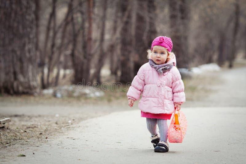 Den allvarliga härliga flickan som går med handväskan i vår, parkerar arkivbilder