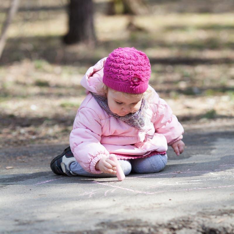 Den allvarliga härliga nätta flickan drar krita i vår parkerar fotografering för bildbyråer