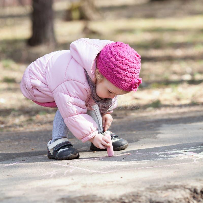 Den allvarliga härliga nätta flickan drar krita i vår parkerar arkivfoto
