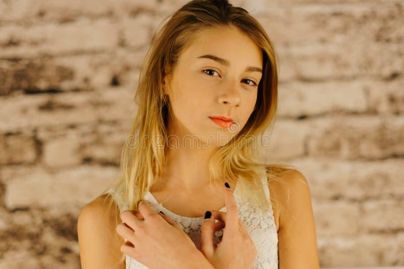Den allvarliga härliga tonårs- flickan med blont hår tät stående upp royaltyfri bild