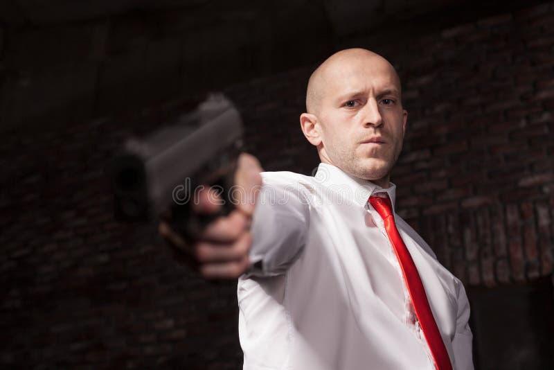 Den allvarliga hyrda mördaren i rött band siktar ett vapen royaltyfria bilder