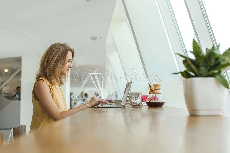 Den allvarliga kvinnan dricker kaffe och arbete arkivfoto