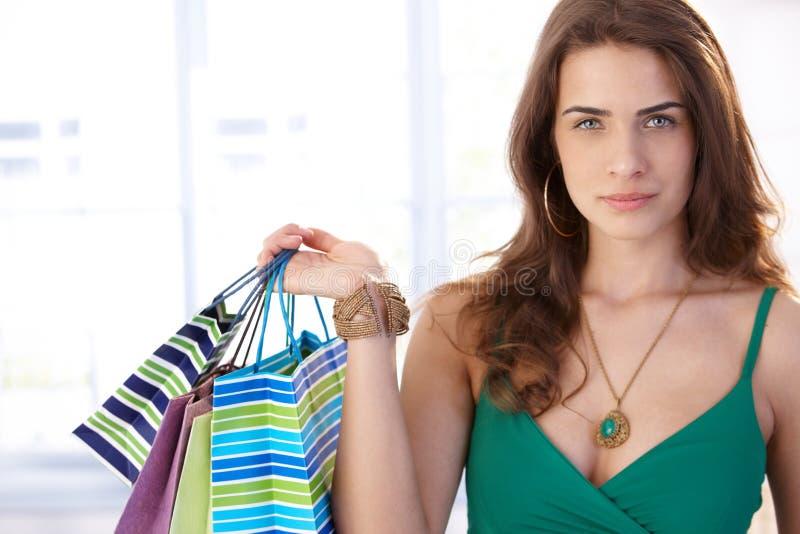Den allvarliga kvinnan med shopping hänger lös royaltyfri foto