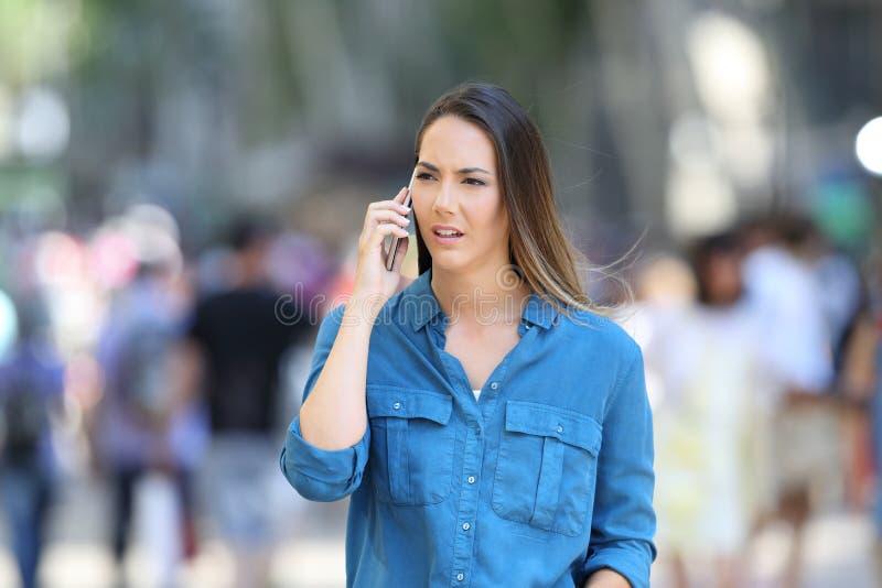 Den allvarliga kvinnan talar på telefonen på gatan royaltyfri foto