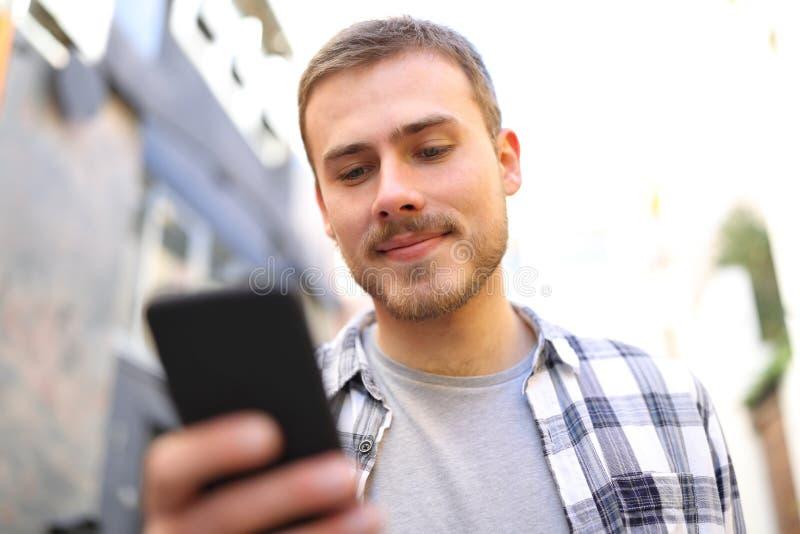 Den allvarliga mannen går genom att använda den smarta telefonen i gatan arkivfoto