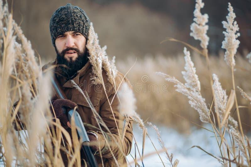 Den allvarliga mannen håller ögonen på på fåglar för att döda dem royaltyfri fotografi