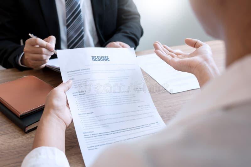 Den allvarliga mannen har ett affärsmöte som läser en meritförteckning om att hyra beslut under en jobbintervju i företaget som ä arkivfoto