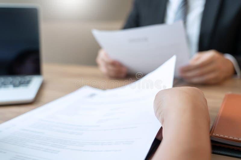 Den allvarliga mannen har ett affärsmöte som läser en meritförteckning om att hyra beslut under en jobbintervju i företaget som ä arkivbild