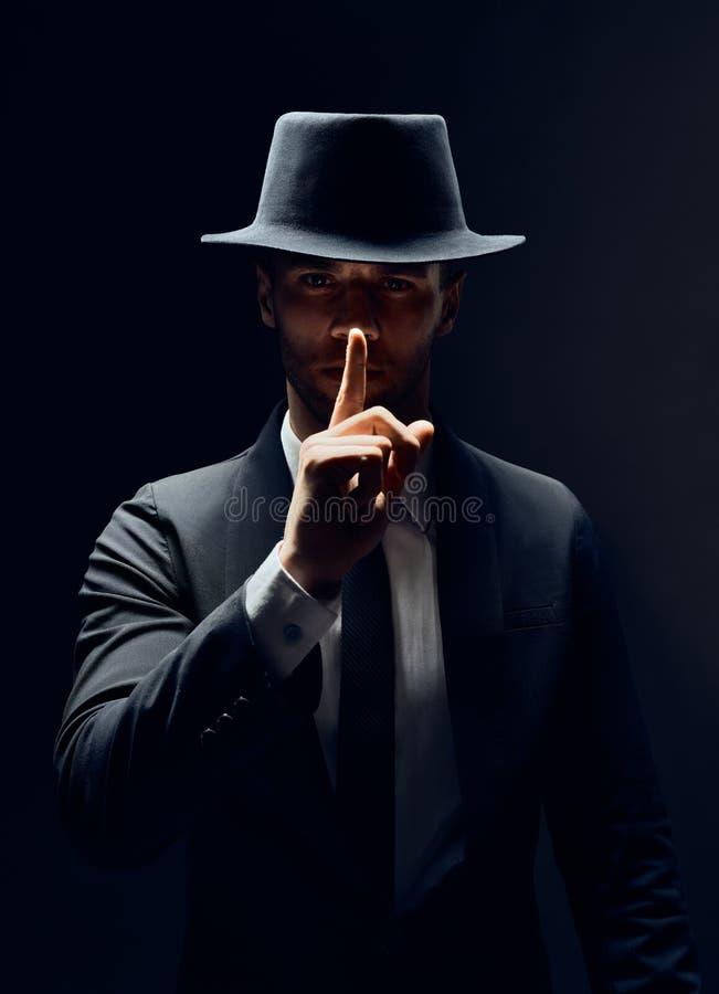 Den allvarliga mannen i svarta dräkt- och hattuppehällen fingrar på kanter och att göra hyssja gesten och att hålla komplott isol arkivfoton