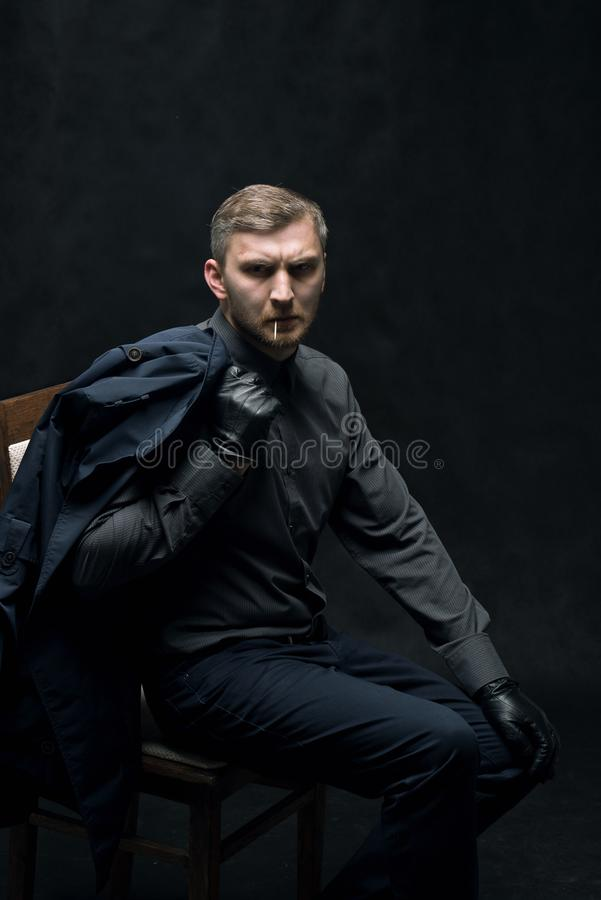 Den allvarliga mannen i svarta läderhandskar sitter på en stol royaltyfri fotografi
