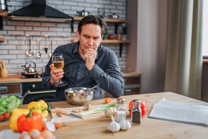 Den allvarliga mannen lutar till tabellen i kök och blick ner Han rymmer exponeringsglas av vitt vin och handen på hakan färgrika royaltyfria foton