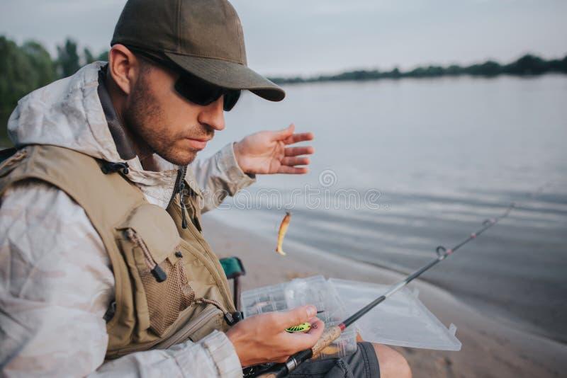 Den allvarliga mannen med solglasögon sitter på kanten av vatten och ser ner Han rymmer skeden med bete Den klipska stången är royaltyfria foton