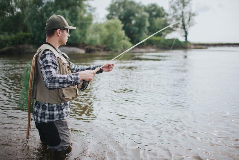 Den allvarliga mannen står, i vatten och att fiska Han har snurr i händer och fisknät på baksidan Grabben bär västen fotografering för bildbyråer
