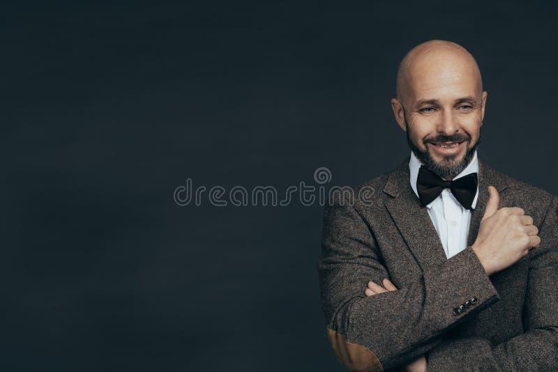 Den allvarliga medel?ldersa mannen med ett ikl?tt tillf?lligt f?r leende poserar p? ett m?rkt - gr? bakgrund fotografering för bildbyråer