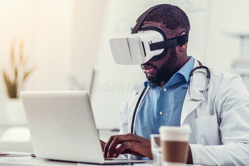 Den allvarliga medicinska arbetaren i VR rullar med ögonen arbete på bärbara datorn fotografering för bildbyråer