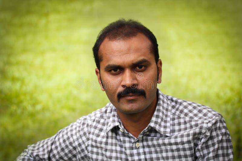 Den allvarliga och beslutsamma indiska mannen sköt på utomhus royaltyfri fotografi