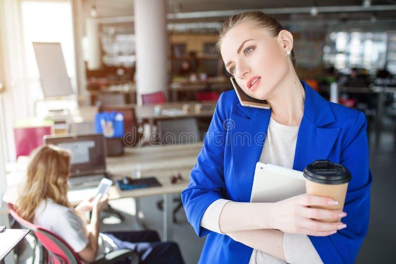Den allvarliga och fundersamma personen talar på telefonen Hon rymmer en kopp kaffe och en anteckningsbok Flickan ser till royaltyfri foto