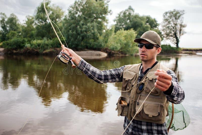 Den allvarliga och koncentrerade mannen står i vatten och rymmer fluga-fiske med rullen under den i en hand och del av skeden in royaltyfri fotografi