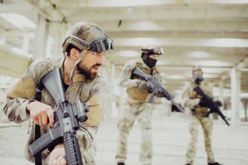 Den allvarliga och starka mördaren står med andra två soldater i en komma med och ett långt rum och ser till rätten dem arkivfoton