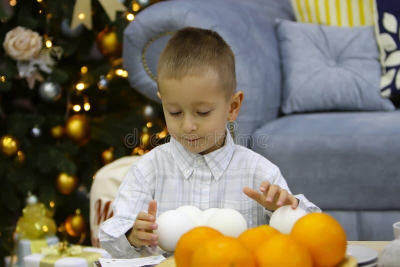 Den allvarliga pojken som står i ett stilfullt rum, lek med, fejkar snö nära julgranen royaltyfria bilder