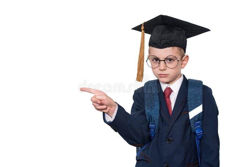 Den allvarliga skolpojken i en dräkt, exponeringsglas och en akademisk hatt pekar hans finger skola f?r copyspace f?r begrepp f?r fotografering för bildbyråer