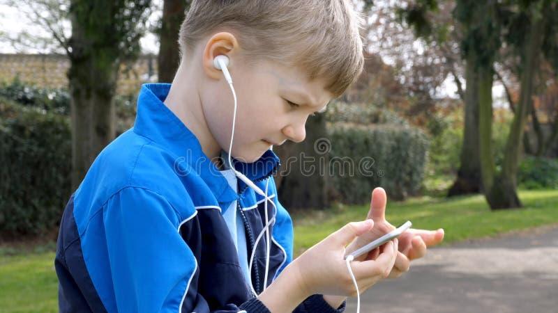 Den allvarliga tonåriga pojken med den smarta telefonen som lyssnar eller talar i brittiskt, parkerar r arkivbild