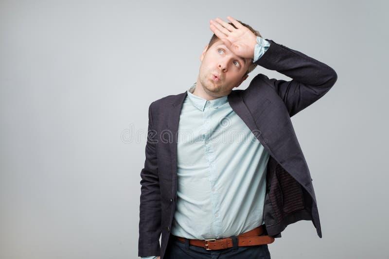 Den allvarliga unga europeiska mannen är trött efter hård arbetsdagspå kontoret arkivfoton