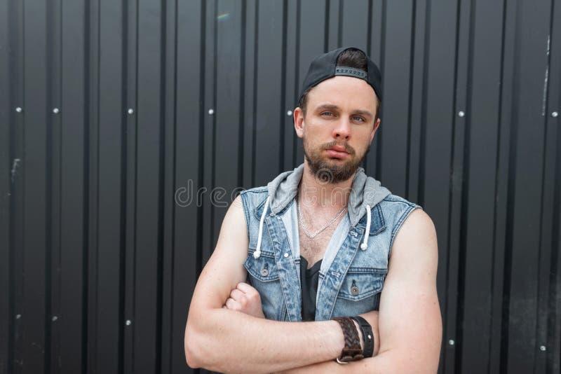 Den allvarliga unga hipstermannen i en trendig blå grov bomullstvill tilldelar en svart t-skjorta med ett skägg i ett stilfullt l royaltyfri fotografi