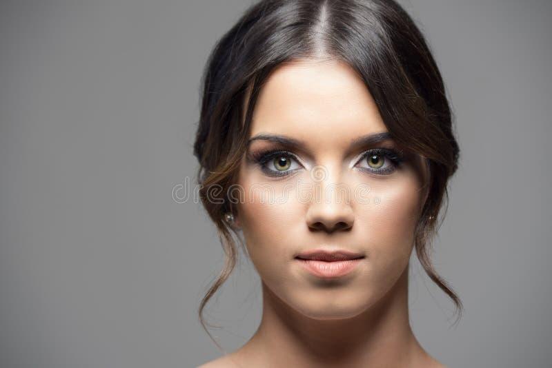 Den allvarliga unga kvinnan med gröna ögon och smokey synar makeup som ser kameran arkivbild