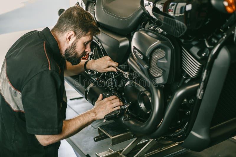 Den allvarliga unga mannen som reparerar hans motorcykel i cykelreparation, shoppar arkivbild