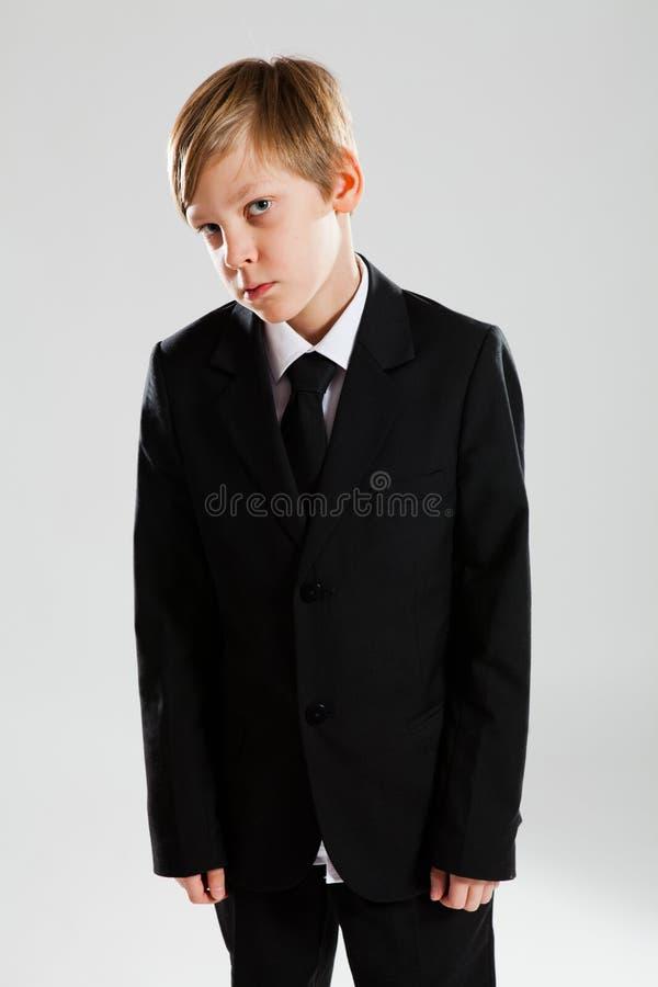 Den allvarliga unga pojken som ha på sig svart, passar arkivbild